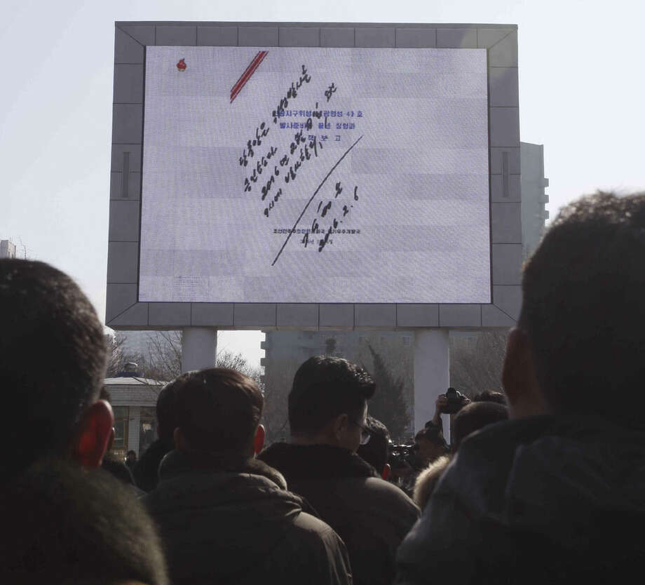 North Koreans watch an electronic screen showing a signed document by North Korean leader Kim Jong Un regarding the launch of a satellite on Sunday, Feb. 7, 2016, at the Pyongyang Railway Station in Pyongyang, North Korea. North Korea on Sunday defied international warnings and launched a long-range rocket that the United Nations and others call a cover for a banned test of technology for a missile that could strike the U.S. mainland. (AP Photo/Kim Kwang Hyon)