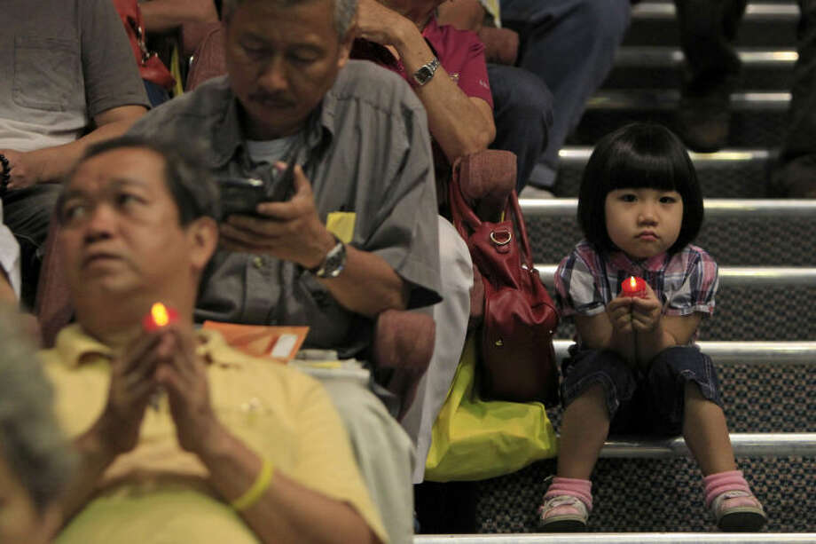 A girl holding a LED candle as she joins a mass prayer for the missing Malaysia Airlines Flight MH370, in Kuala Lumpur, Malaysia, Sunday, April 6, 2014. The head of the multinational search for the missing Malaysia airlines jet said that electronic pulses reportedly picked up by a Chinese ship are an encouraging sign but stresses they are not yet verified. (AP Photo/Lai Seng Sin)
