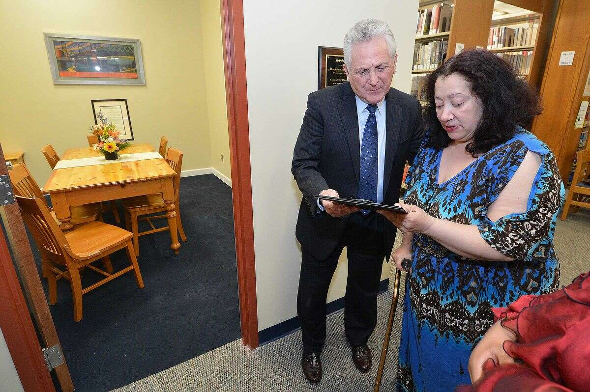 Hour Photo/Alex von Kleydorff Judy Rivas sister Migdalia Rivas holds a plaque from the United Nations, The Pura Belpre Award for her sister as Mayor Harry Rilling reads it during an opening reception for Judy's Room at The Norwalk Public Library