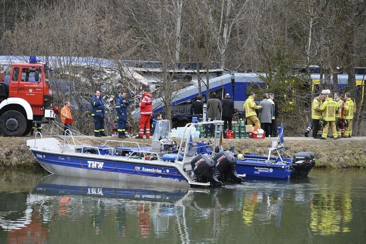 Rescue personnel stand in front of two trains that collided head-on near Bad Aibling, southern Germany, Tuesday, Feb. 9, 2016. Several people have been killed and dozens were injured. (AP Photo/Kerstin Joensson)