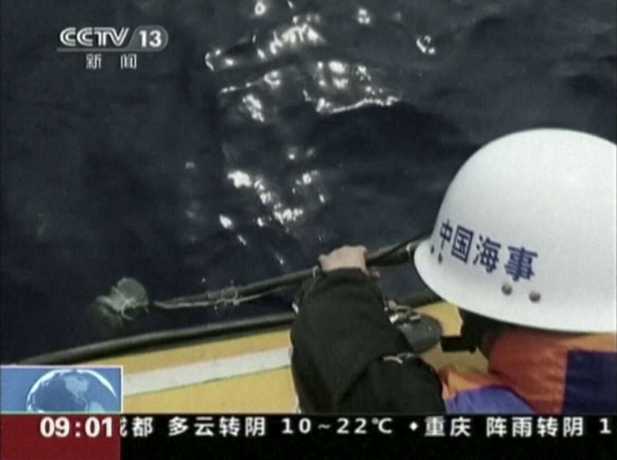 """In this image taken from video, a member of a Chinese search team uses an instrument to detect electronic pulses while searching for the missing Malaysia Airlines Flight 370, on board the patrol vessel Haixun 01, in the search area in the southern Indian Ocean, Saturday, April 5, 2014. China's official Xinhua News Agency reported late Saturday that the patrol vessel Haixun 01 had detected a """"pulse signal"""" at 37.5 kilohertz (cycles per second) - the same frequency emitted by flight data recorders aboard the missing plane - in the search area in the southern Indian Ocean. But retired Australian Air Chief Marshall Angus Houston stressed the two electronic pulses that the Chinese ship reported detecting on Friday and Saturday had not been verified as connected to the missing jet. (AP Photo/CCTV via AP Video)"""