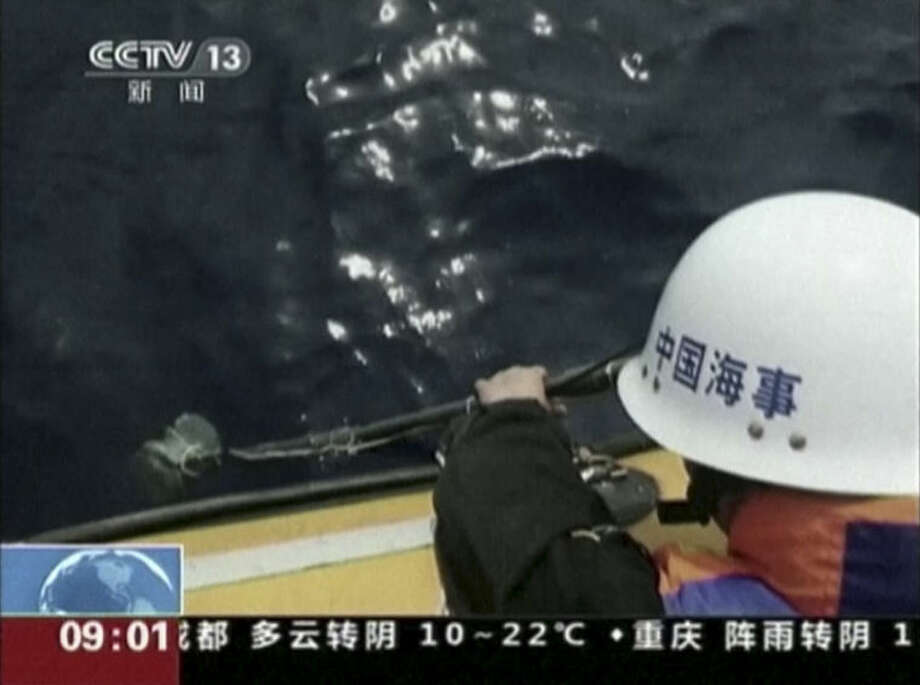 "In this image taken from video, a member of a Chinese search team uses an instrument to detect electronic pulses while searching for the missing Malaysia Airlines Flight 370, on board the patrol vessel Haixun 01, in the search area in the southern Indian Ocean, Saturday, April 5, 2014. China's official Xinhua News Agency reported late Saturday that the patrol vessel Haixun 01 had detected a ""pulse signal"" at 37.5 kilohertz (cycles per second) - the same frequency emitted by flight data recorders aboard the missing plane - in the search area in the southern Indian Ocean. But retired Australian Air Chief Marshall Angus Houston stressed the two electronic pulses that the Chinese ship reported detecting on Friday and Saturday had not been verified as connected to the missing jet. (AP Photo/CCTV via AP Video)"