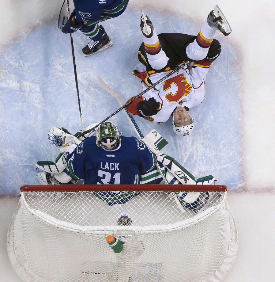 Calgary Flames center Sam Bennett (63) hits the ice as Vancouver Canucks goalie Eddie Lack (31) defends during the first period of Game 1 of an NHL hockey first-round playoff series, Wednesday, April 15, 2015, in Vancouver, British Columbia. (Jonathan Hayward/The Canadian Press via AP)