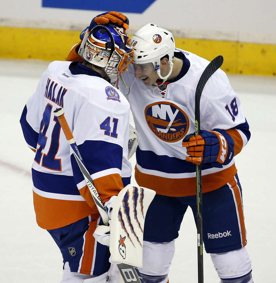 New York Islanders goalie Jaroslav Halak (41), from Slovakia, and center Ryan Strome celebrate after a 4-1 win over the Washington Capitals in the opening game of a first-round NHL hockey playoff series, Wednesday, April 15, 2015, in Washington. (AP Photo/Alex Brandon)