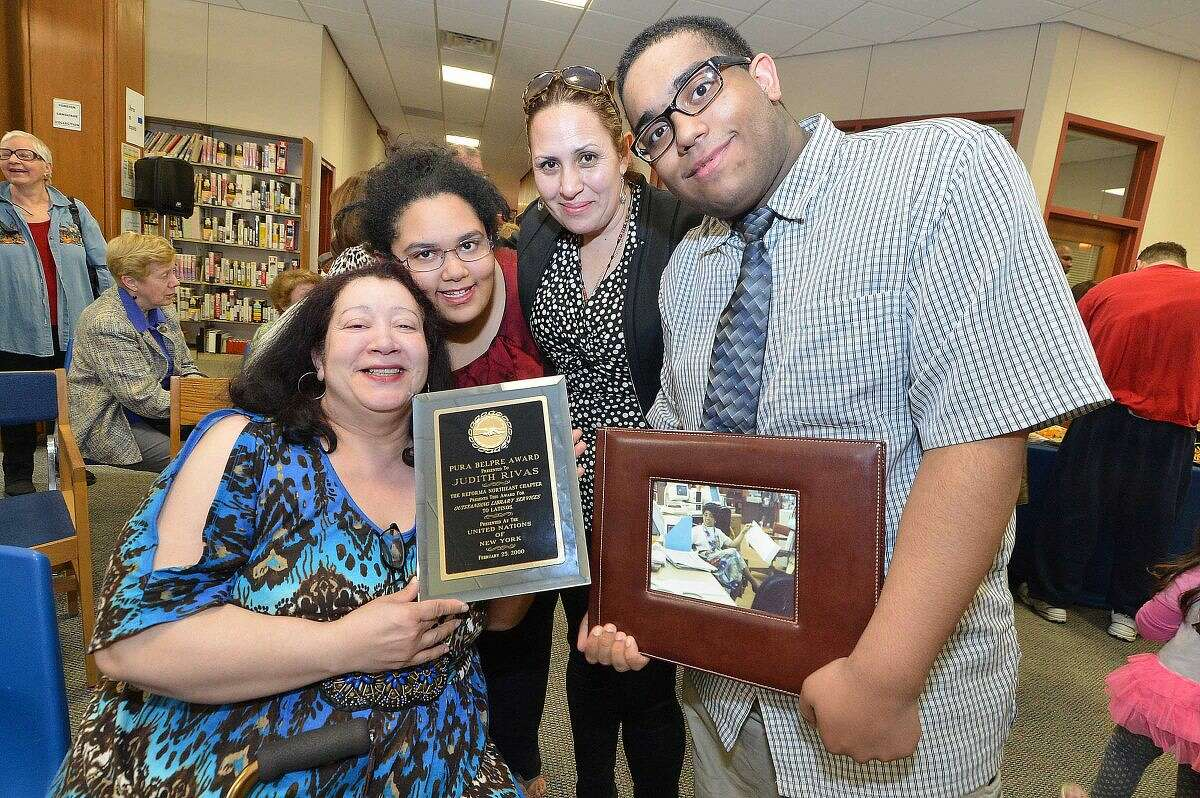 Hour Photo/Alex von Kleydorff Judy Rivas sister Migdalia Rivas holds a plaque, The Pura Belpre Award from the United Nation for her sister and is joined by Judy's Neice Jessica Joseph, Judy's best friend Faviola Espinoza and Judy's nephew Daniel Joseph holding a photo of his Aunt during the opening of a room dedicated to her at the Norwalk Public Library