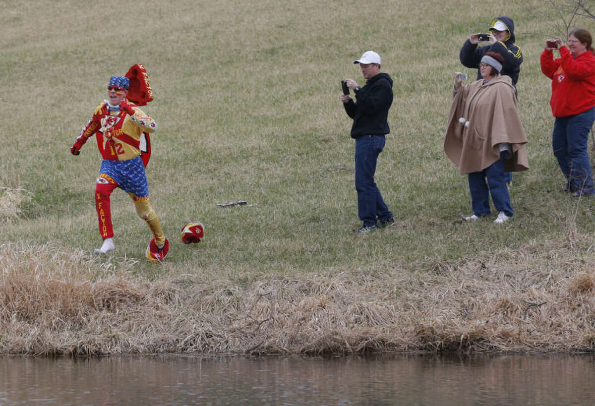 Kansas City Chiefs fan Ty Rowton, known as XFactor, is videoed by friends as he takes a Plunge for Landon in a farm pond near Bonner Springs, Kan., Friday, April 4, 2014. A 5-month-old boy's battle with cancer has inspired hundreds to jump into cold bodies of water, from a local golf course pond to the Gulf of Mexico and even the Potomac River in Washington, D.C. (AP Photo/Orlin Wagner)