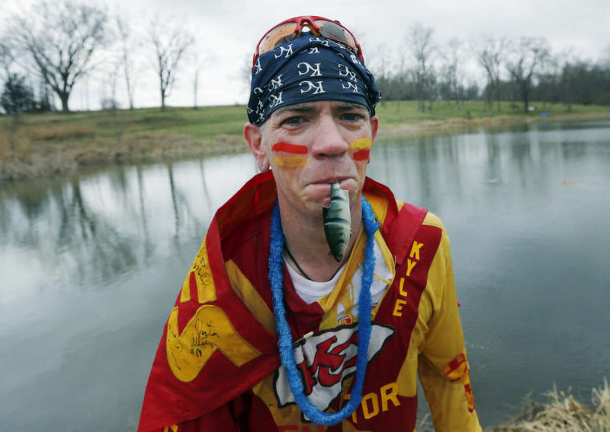 Kansas City Chiefs fan Ty Rowton, known as XFactor, exits the water with a toy fish in his mouth after takeing a Plunge for Landon in a farm pond near Bonner Springs, Kan., Friday, April 4, 2014. A 5-month-old boy's battle with cancer has inspired hundreds to jump into cold bodies of water, from a local golf course pond to the Gulf of Mexico and even the Potomac River in Washington, D.C. (AP Photo/Orlin Wagner)