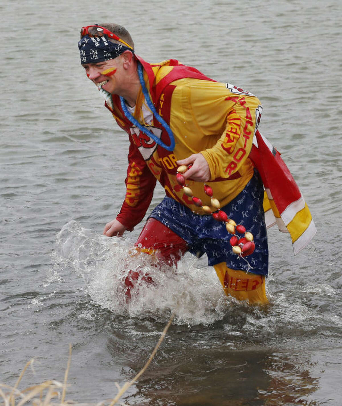 Kansas City Chiefs fan Ty Rowton, known as XFactor, retrieves part of his costume after takeing a Plunge for Landon in a farm pond near Bonner Springs, Kan., Friday, April 4, 2014. A 5-month-old boy's battle with cancer has inspired hundreds to jump into cold bodies of water, from a local golf course pond to the Gulf of Mexico and even the Potomac River in Washington, D.C. (AP Photo/Orlin Wagner)
