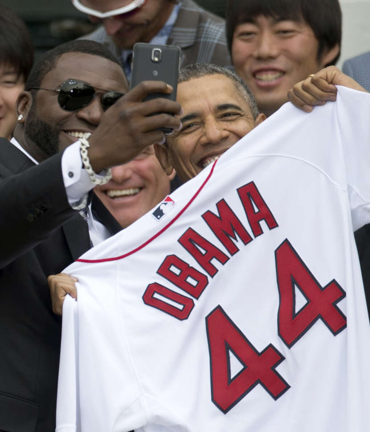 """Boston Red Sox designated hitter David """"Big Papi"""" Ortiz takes a selfie with President Barack Obama, holding a Boston Red Sox jersey presented to him, during a ceremony on the South Lawn of the White House in Washington, Tuesday, April 1, 2014, where the president honored the 2013 World Series baseball champion Boston Red Sox. In the background is pitcher Koji Uehara, upper right. (AP Photo/Carolyn Kaster)"""