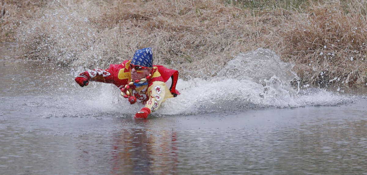 Kansas City Chiefs fan Ty Rowton, known as XFactor, takes a Plunge for Landon in a farm pond near Bonner Springs, Kan., Friday, April 4, 2014. A 5-month-old boy's battle with cancer has inspired hundreds to jump into cold bodies of water, from a local golf course pond to the Gulf of Mexico and even the Potomac River in Washington, D.C. (AP Photo/Orlin Wagner)