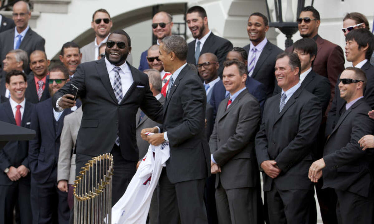 """Boston Red Sox designated hitter David """"Big Papi"""" Ortiz, left, laughs, after taking a selfie with President Barack Obama, holding a Boston Red Sox jersey presented to the president, Tuesday, April 1, 2014, during a ceremony on the South Lawn of the White House in Washington where the president honored the 2013 World Series baseball champion Boston Red Sox. (AP Photo/Manuel Balce Ceneta)"""