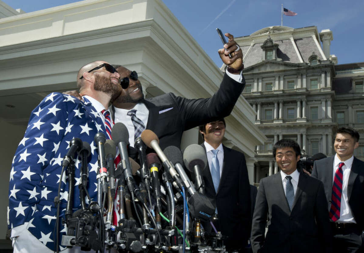 """Boston Red Sox designate hitter David """"Big Papi"""" Ortiz, second from left, takes a selfie with teammate Johnny Gomes, outside White House in Washington, Tuesday, April 1, 2014, following a ceremony where President Barack Obama honored the 2013 World Series baseball champion Boston Red Sox. (AP Photo/Manuel Balce Ceneta)"""