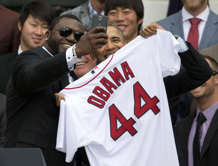 "Boston Red Sox player David ""Big Papi"" Ortiz takes a selfie with President Barack Obama, holding a Boston Red Sox jersey presented to the president during a ceremony on the South Lawn of the White House in Washington, Tuesday, April 1, 2014, where the president honored the 2013 World Series baseball champion Boston Red Sox. In the background are pitchers Junichi Tazawa, left, Koji Uehara, right. (AP Photo/Carolyn Kaster)"