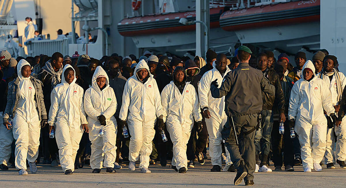 """Migrants are transferred to holding centers after disembarking from Italian Coast Guard ship """"Dattilo"""", in Augusta's port, near Siracusa, Sicily, Italy, Thursday, April 16, 2015. An unprecedented wave of migrants has headed for the European Union's promised shores over the past week, with 10,000 people making the trip. Hundreds - nobody knows how many - have disappeared into the warming waters of the Mediterranean, including 41 migrants reported dead Thursday after a shipwreck. (AP Photo/Carmelo Imbesi)"""