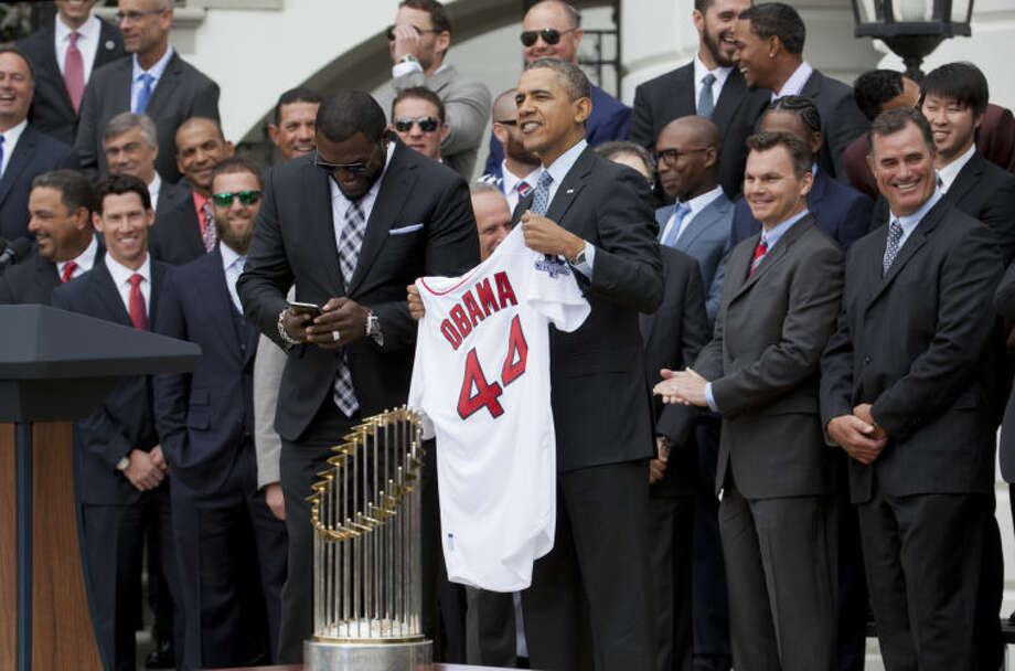 """Boston Red Sox designated hitter David """"Big Papi"""" Ortiz, left, takes out his phone to take a selfie with President Barack Obama, holding a Boston Red Sox jersey presented to the president during a ceremony on the South Lawn of the White House in Washington, Tuesday, April 1, 2014, where the president honored the 2013 World Series baseball champion Boston Red Sox. (AP Photo/Manuel Balce Ceneta)"""