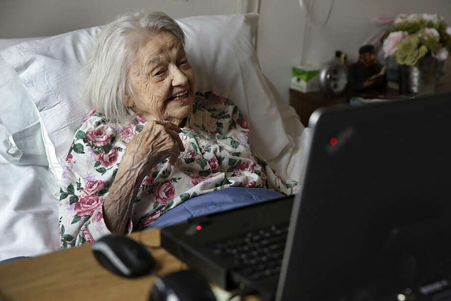 Patient Louise Irving watches a laptop computer with her daughter's morning wake-up video playing, at The Hebrew Home of Riverdale, in New York, Wednesday, March 25, 2015. The nursing home in the Bronx has started a pilot program in which relatives record video messages for patients of Alzheimer's and other forms of dementia. The videos are played for them each morning to calm their agitation and reassure them about their surroundings and their routines. (AP Photo/Richard Drew)