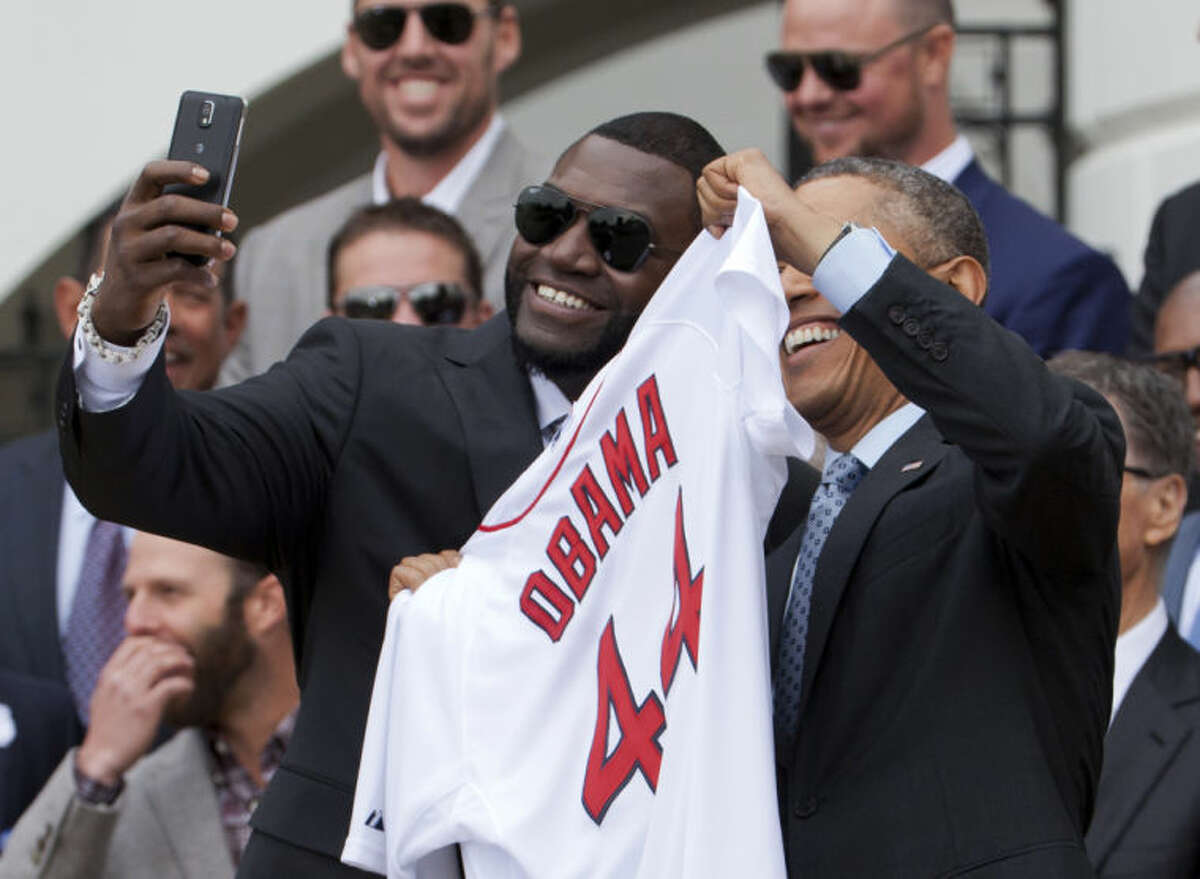 """Boston Red Sox designated hitter David """"Big Papi"""" Ortiz, left, takes a selfie with President Barack Obama, holding a Boston Red Sox jersey presented to the president during a ceremony on the South Lawn of the White House in Washington, Tuesday, April 1, 2014, where the president honored the 2013 World Series baseball champion Boston Red Sox. (AP Photo/Manuel Balce Ceneta)"""