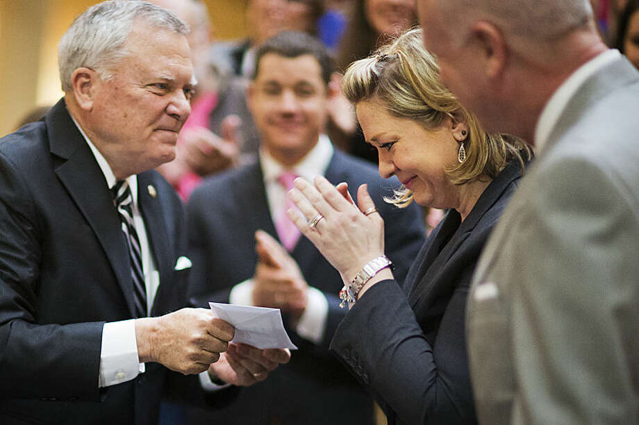"""Janea Cox, right, is handed the first temporary registration card by Georgia Gov. Nathan Deal after he signed a medical marijuana bill, also known as """"Haleigh's Hope Act"""" after Cox's five-year-old daughter, Haleigh, who suffers from seizures, during a ceremony at the Statehouse, Thursday, April 16, 2015, in Atlanta. The bill makes Georgia the 38th state to have one and legalizes possession of cannabis oil for treatment of certain medical conditions. (AP Photo/David Goldman)"""