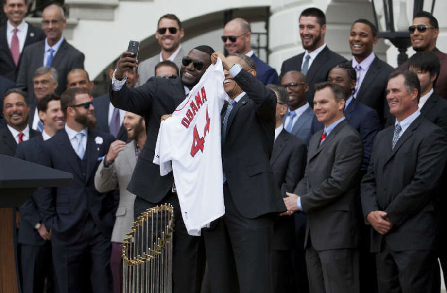 """Boston Red Sox player David """"Big Papi"""" Ortiz, left, takes a selfie with President Barack Obama, holding a Boston Red Sox jersey presented to the president during a ceremony on the South Lawn of the White House in Washington, Tuesday, April 1, 2014, where the president honored the 2013 World Series baseball champion Boston Red Sox. (AP Photo/Manuel Balce Ceneta)"""