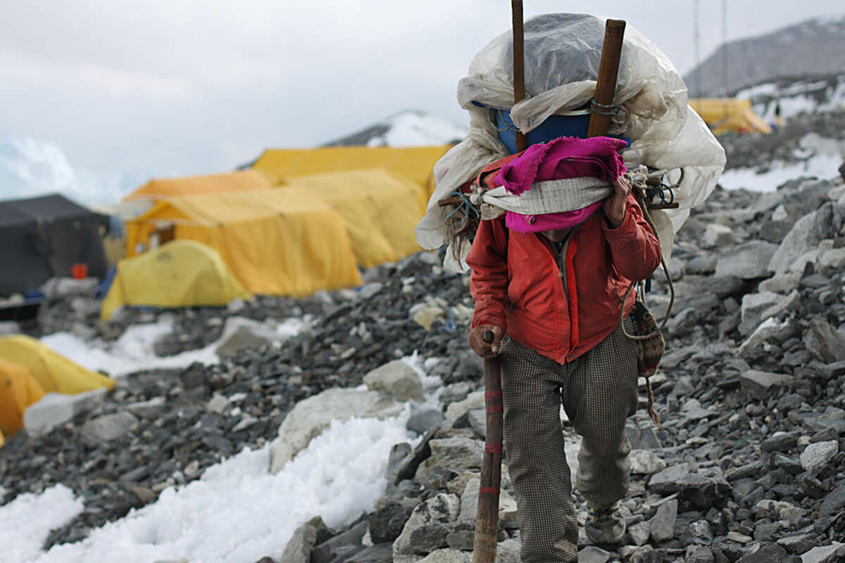 In this Saturday, April 11, 2015 photo, porter walks with supplies at Everest Base Camp in Nepal. Saturday, April 18 marks the first year anniversary of an ice avalanche that killed 16 guides in the mountain's deadliest disaster. (AP Photo/Tashi Sherpa)