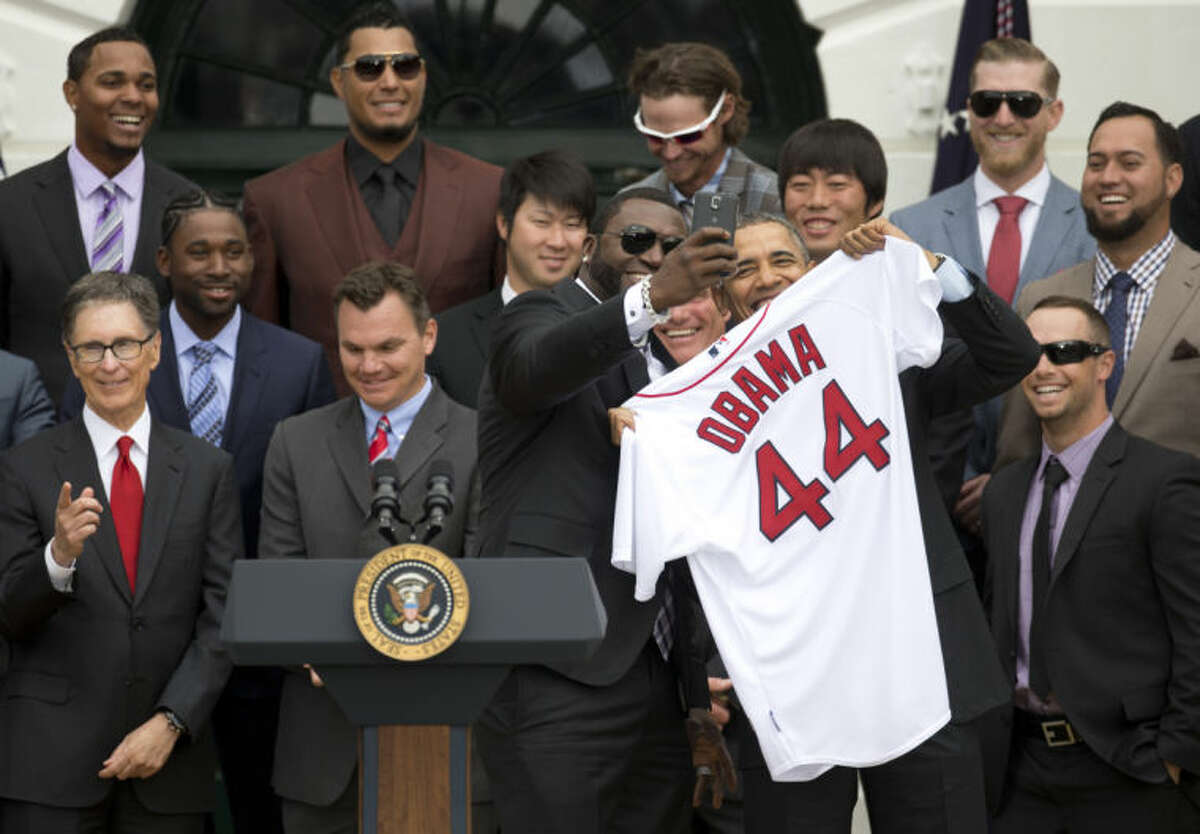 """Boston Red Sox designated hitter David """"Big Papi"""" Ortiz takes a selfie with President Barack Obama, holding a Boston Red Sox jersey, as the president Obama honored the 2013 World Series baseball champion Boston Red Sox, Tuesday, April 1, 2014, during a ceremony on the South Lawn of the White House in Washington. Front row, from left are : Boston Red Sox owner John Henry, General Manager Ben Cherington, Ortiz, the president, and Daniel Nava. Second row, from left are: Jackie Bradley Jr., Junichi Tazawa, Koji Uehara, Edward Mujica. Third row, from left are: Xander Bogaerts, Felix Doubront, Clay Buccholz, and Mike Carp. (AP Photo/Carolyn Kaster)"""