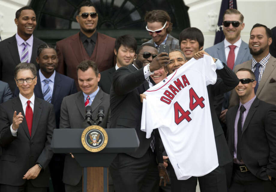 "Boston Red Sox designated hitter David ""Big Papi"" Ortiz takes a selfie with President Barack Obama, holding a Boston Red Sox jersey, as the president Obama honored the 2013 World Series baseball champion Boston Red Sox, Tuesday, April 1, 2014, during a ceremony on the South Lawn of the White House in Washington. Front row, from left are : Boston Red Sox owner John Henry, General Manager Ben Cherington, Ortiz, the president, and Daniel Nava. Second row, from left are: Jackie Bradley Jr., Junichi Tazawa, Koji Uehara, Edward Mujica. Third row, from left are: Xander Bogaerts, Felix Doubront, Clay Buccholz, and Mike Carp. (AP Photo/Carolyn Kaster)"