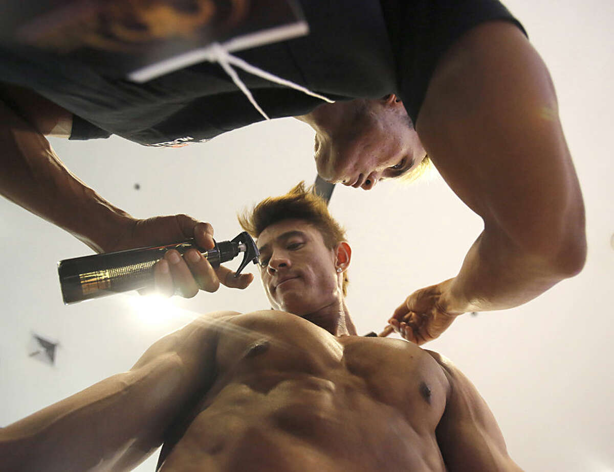 A competitor gets sprayed with fake tan paint before the Mr. Thailand 2015 bodybuilding competition in Bangkok, Thailand, Friday, April 17, 2015. The three-day competition attracts more than 400 bodybuilding enthusiasts across the country. (AP Photo/Sakchai Lalit)