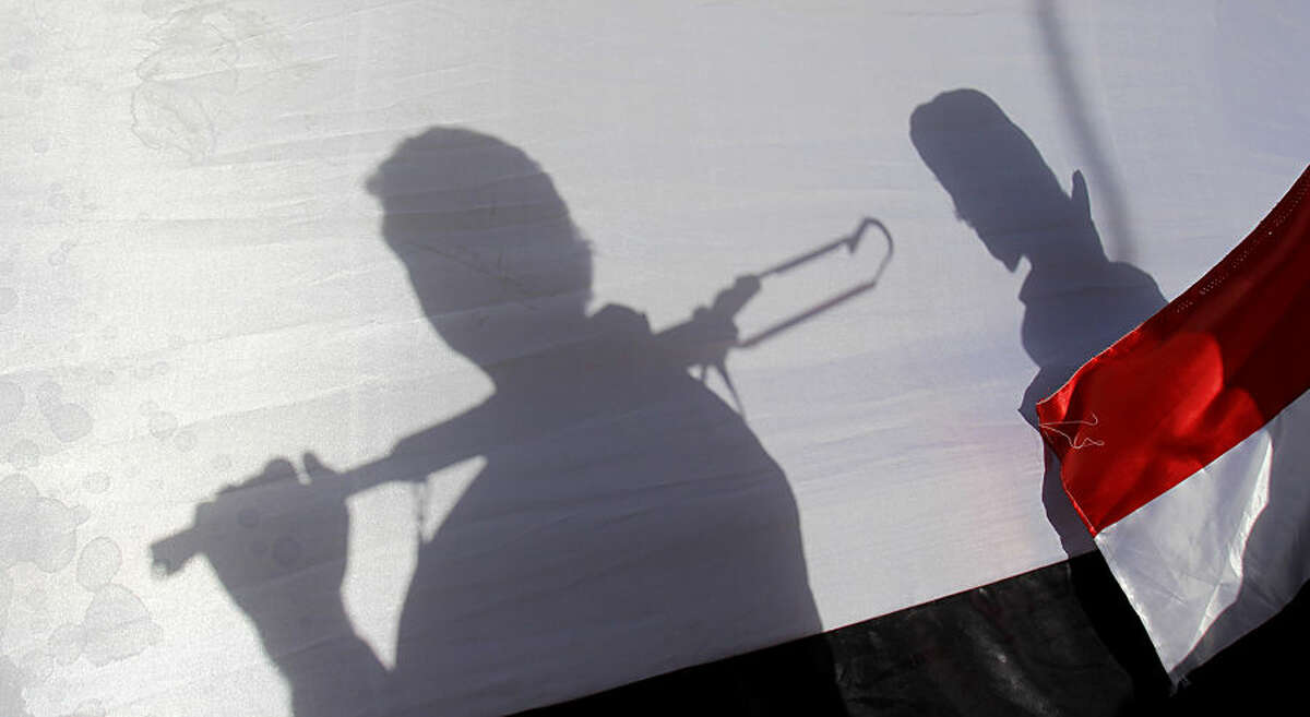 The shadow of Shiite rebels, known as Houthis, are cast on a large representation of the Yemeni flag as they attend a demonstration against an arms embargo imposed by the U.N. Security Council on Houthi leaders, in Sanaa, Yemen, Thursday, April 16, 2015. Al-Qaida's branch in Yemen seized Thursday control of a major airport and sea port and oil terminal in southern Yemen, consolidating their hold of the country's largest province amid wider chaos that is pitting Shiite rebels against forces loyal to the country's exiled president and a Saudi-led air campaign.(AP Photo/Hani Mohammed)