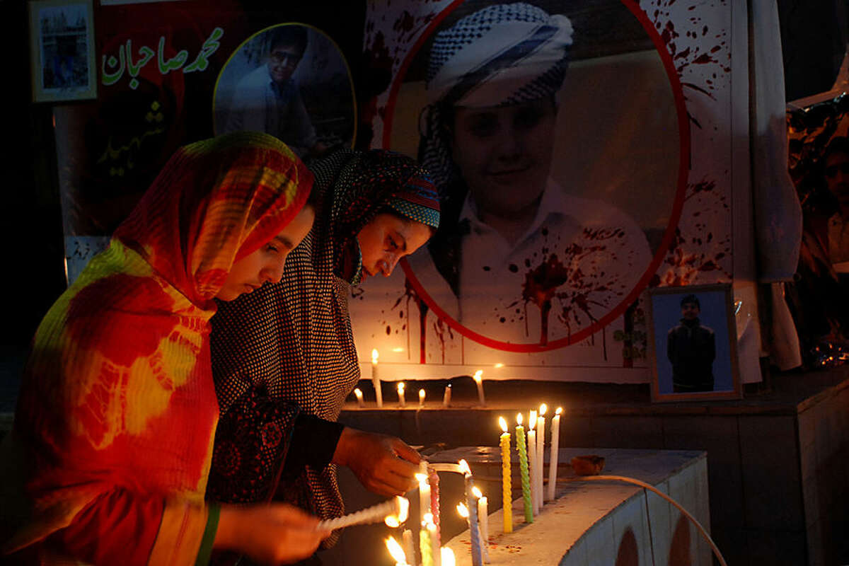 Family members of slain students, light candles to pay tribute to students and others who were killed in an attack on a school last year by Taliban gunmen and registered their protest against slow investigation, in Peshawar, Pakistan, Thursday, April 16, 2015. Pakistani Taliban militants attacked an army-run school in Peshawar, killing 150 people, mostly children. (AP Photo/Mohammad Sajjad)