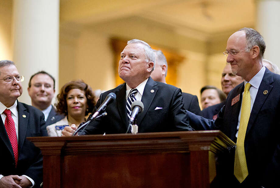 Georgia Gov. Nathan Deal, center, fights back tears while speaking after signing a medical marijuana bill into law as the bill sponsor, Rep. Allen Peake, R-Macon, right, looks on during a ceremony at the Statehouse, Thursday, April 16, 2015, in Atlanta. The bill makes Georgia the 38th state to have one and legalizes possession of cannabis oil for treatment of certain medical conditions. (AP Photo/David Goldman)