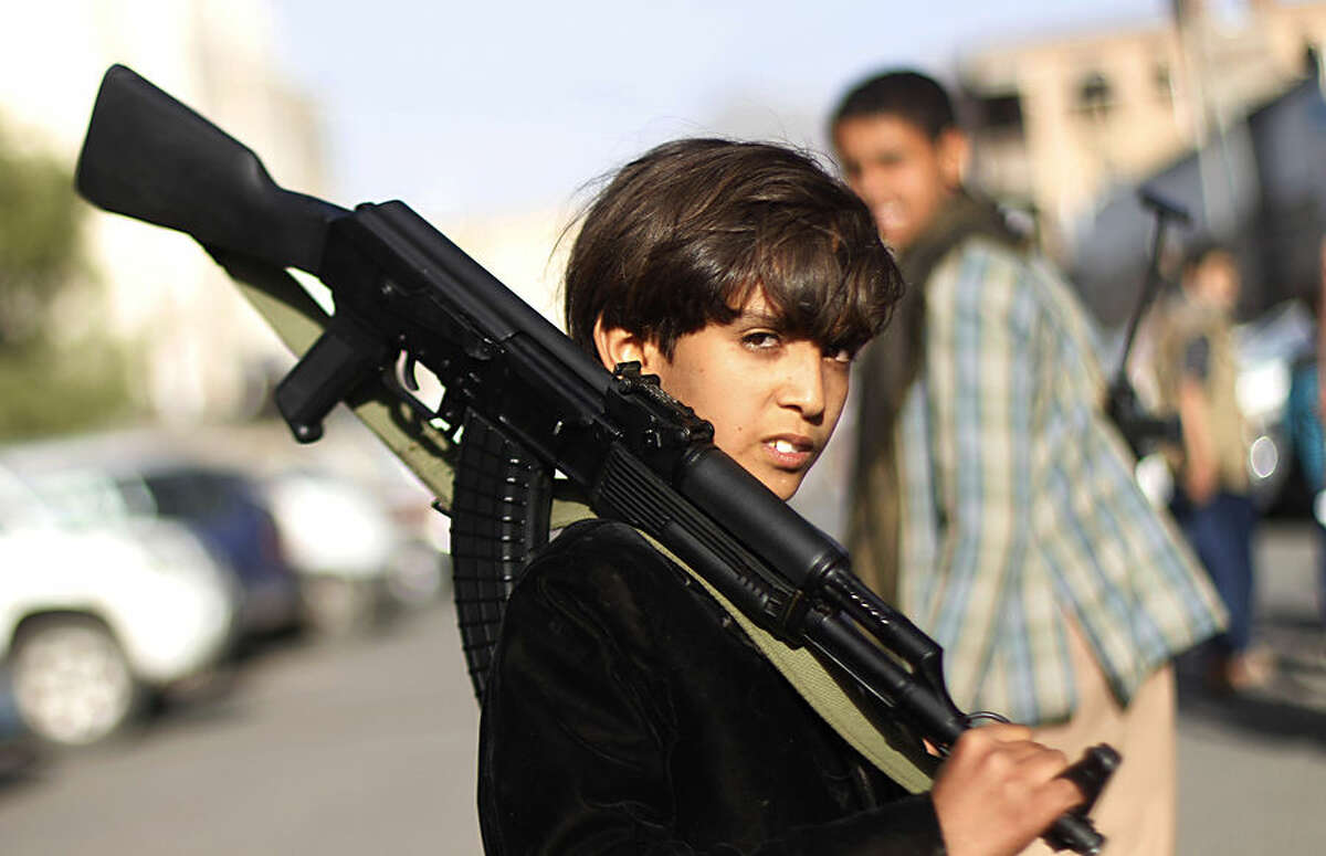 A Yemeni boy holding a weapon poses for a picture during a demonstration against an arms embargo imposed by the U.N. Security Council on Houthi leaders, in Sanaa, Yemen, Thursday, April 16, 2015. Al-Qaida's branch in Yemen seized Thursday control of a major airport and sea port and oil terminal in southern Yemen, consolidating their hold of the country's largest province amid wider chaos that is pitting Shiite rebels against forces loyal to the country's exiled president and a Saudi-led air campaign. (AP Photo/Hani Mohammed)