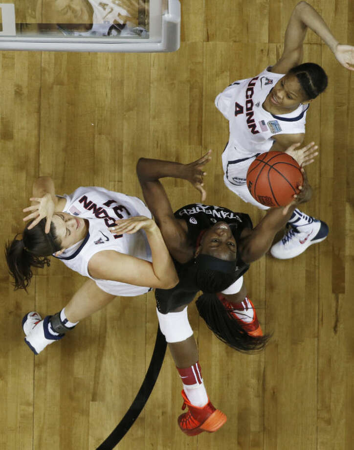 Stanford forward Chiney Ogwumike (13) works between Connecticut's Stefanie Dolson (31) Moriah Jefferson (4) during the second half of the semifinal game in the Final Four of the NCAA women's college basketball tournament, Sunday, April 6, 2014, in Nashville, Tenn. (AP Photo/John Bazemore)