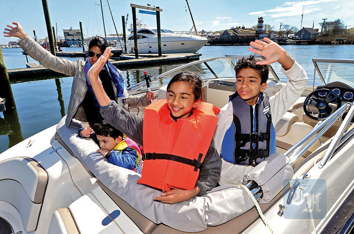 Hour photo / Erik Trautmann Uzma Ahmed, her children Sana and Munir and their guest 3 year old dam Khattak get ready take out their new boat at Veteran's Park Visitors Dock in Norwalk Saturday.