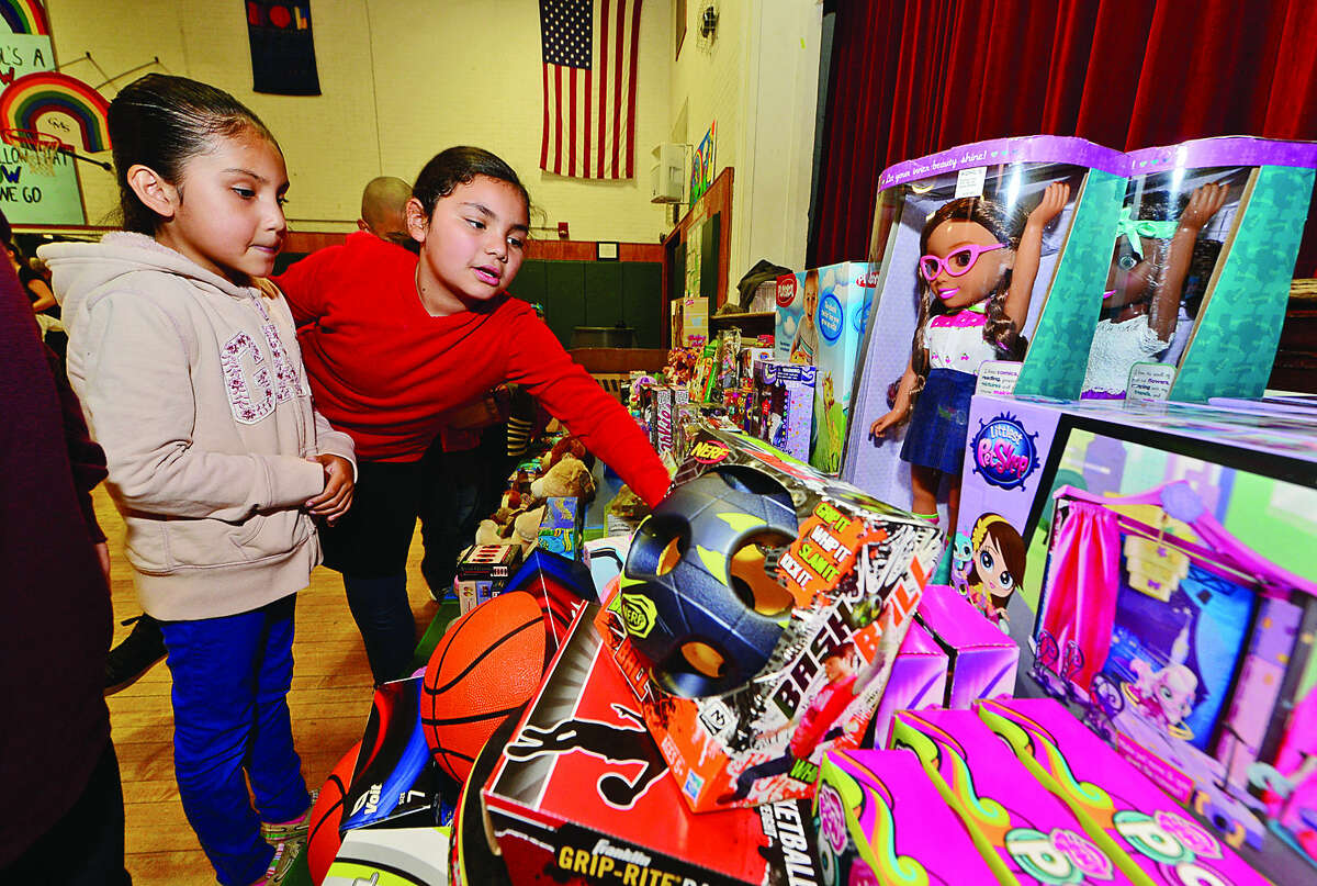 Hour photo / Erik Trautmann Evelyn Trejo-Reyes and Gezelle Oseguera looks over toys on display during The Norwalk Community Policing Division Children's Christmas Party Saturday at Columbus Magnet School.