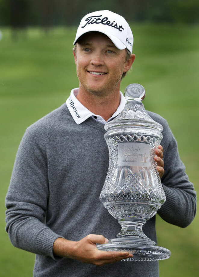 Matt Jones holds the championship trophy after winning the Houston Open golf tournament on Sunday, April 6, 2014, in Humble, Texas. (AP Photo/Patric Schneider)