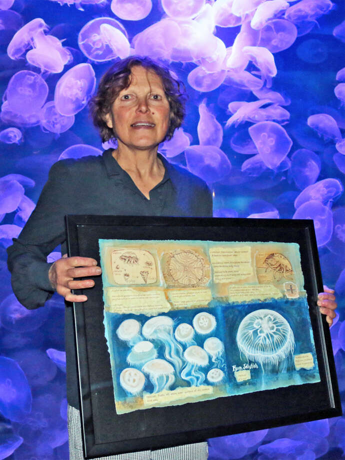"Norwalk artist Lynn Stephens Massey holds her watercolor studies on jellyfish in front of the Maritime Aquarium at Norwalk's exhibit of moon jellies. An exhibit of her paintings of local aquatic life, ""Aqua Marine,"" is display at the aquarium through Saturday. Find out more: http://bit.ly/1SyoIma"