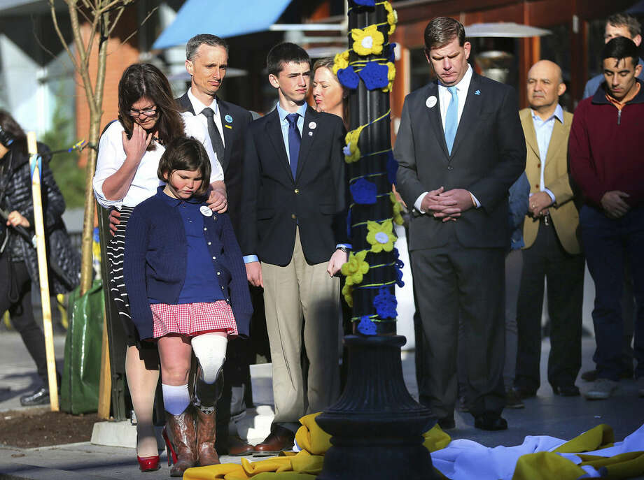 Boston Mayor Marty Walsh, right. looks down after Boston Marathon survivor Jane Richard, left, and her brother Henry removed a drape covering a memorial honoring victims and survivors at one of two blast sites near the finish line of the Boston Marathon in Boston, Wednesday, April 15, 2015. Parents, Bill and Denise Richards, back, stood by during the unveiling. Boston marked the second anniversary of the 2013 marathon bombings with a subdued remembrance that includes a moment of silence, the pealing of church bells and a call for kindness. The children lost their brother Martin Richard while standing with him during one of the explosions. (John Tlumacki/The Boston Globe via AP) BOSTON HERALD OUT, QUINCY OUT; NO SALES