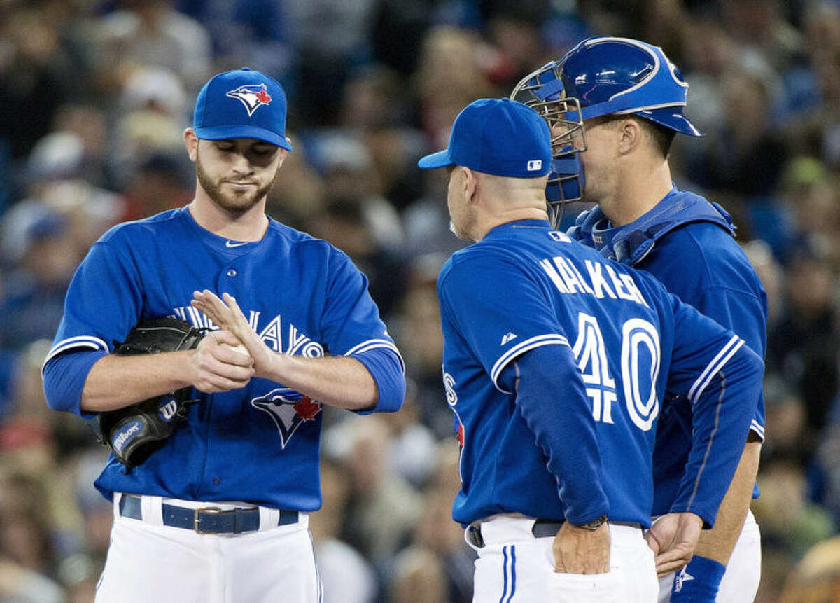 Toronto Blue Jays starting pitcher Drew Hutchison, left, talks with Blue Jays pitching coach Pete Walker (40) and catcher Erik Kratz, right, while playing against the New York Yankees during the first inning of a baseball game in Toronto on Sunday, April 6, 2014. (AP Photo/The Canadian Press, Nathan Denette)
