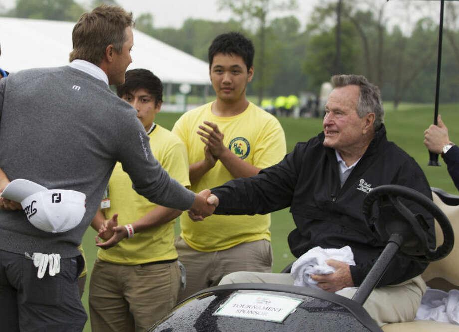 Former President George H. W. Bush congratulates Matt Jones after Jones won the Houston Open golf tournament, Sunday, April 6, 2014, in Humble, Texas. (AP Photo/Patric Schneider)
