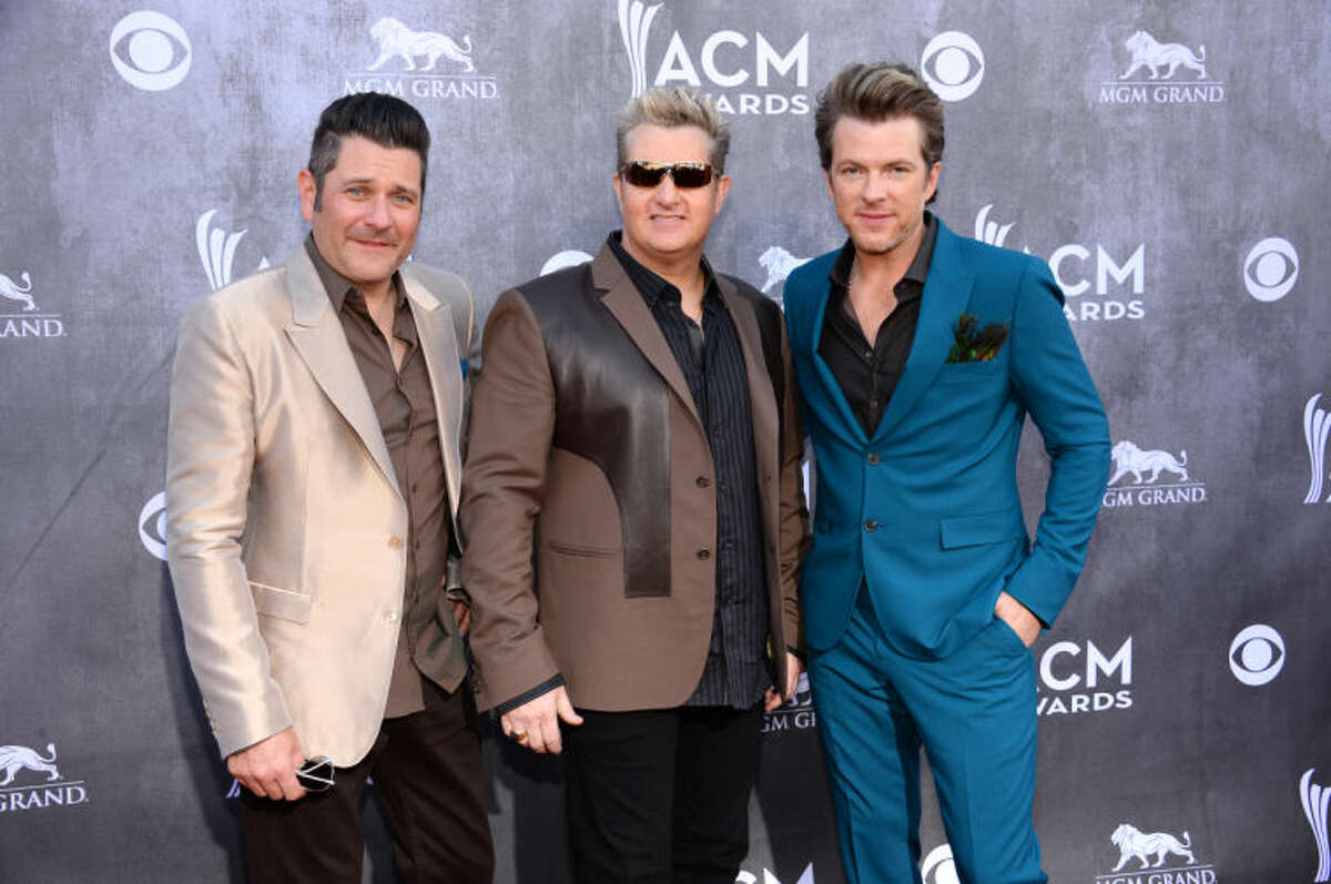 Jay DeMarcus, and from left, Gary LeVox and Joe Don Rooney, of the musical group Rascal Flatts, arrive at the 49th annual Academy of Country Music Awards at the MGM Grand Garden Arena on Sunday, April 6, 2014, in Las Vegas. (Photo by Al Powers/Powers Imagery/Invision/AP)