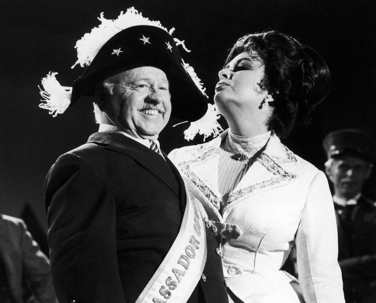 """FILE - In this Thursday, Aug. 27, 1981, file photo, veteran comic Mickey Rooney wears a Napoleonic-era hat as he tapes an """"I love New York"""" television commercial with British-American actress Elizabeth Taylor, in New York. Rooney, a Hollywood legend whose career spanned more than 80 years, has died. He was 93. Los Angeles Police Commander Andrew Smith said that Rooney was with his family when he died Sunday, April 6, 2014, at his North Hollywood home. (AP Photo/GPB, File)"""