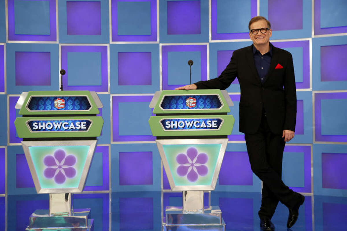 """This 2013 photo released by CBS shows Drew Carey, host of """"The Price is Right,"""" on the set in Los Angeles. On Tuesday, April 7, the game show will air its 8,000th episode since it debuted on CBS in 1972. The concept hasn't changed through the years and it's a nonstop party in the hands of host Drew Carey. (AP Photo/CBS, Cliff Lipson)"""