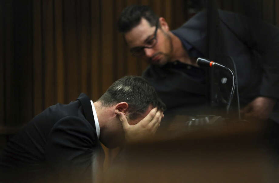 Oscar Pistorius is comforted by his brother Carl, back, as he listens to evidence by a pathologist in court in Pretoria, South Africa, Monday, April 7, 2014. Pistorius is charged with murder for the shooting death of his girlfriend Reeva Steenkamp, on Valentines Day 2013. (AP Photo/Themba Hadebe, Pool)