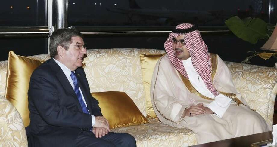 """This image released by the Saudi Press Agency shows Prince Nawaf Faisal Fahd bin Abdul-Aziz, an International Olympic Committee member and president of the national Olympic committee, right,, walking with IOC President Thomas Bach, left, in Riyadh, Saudi Arabia, Wednesday, April 2, 2014. IOC President Thomas Bach has discussed the issue of women's participation in sports with Saudi Arabia's Olympic chief. The IOC says Wednesday that Bach promised """"full support"""" for the country's sports development strategy through 2020. The plan includes """"proposals to increase women's participation in the Olympic Games and in sport in general."""" Saudi women are largely banned from participating in sports in the kingdom, although there are several football and basketball clubs that play in clandestine leagues. After prolonged negotiations with the IOC, Saudi Arabia sent women to the Olympics for the first time in 2012, with two female athletes competing at the London Games. (AP Photo/Saudi Press Agency)"""