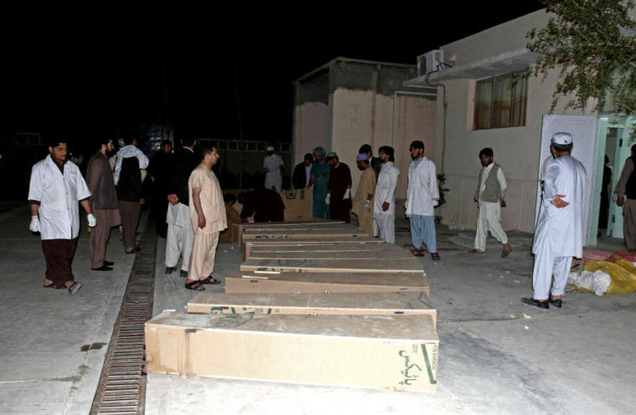 Medics stand around coffins of civilians killed from a roadside bomb at a hospital in Kandahar, south of Kabul, Afghanistan, Monday, April 7, 2014. A roadside bomb killed at least 15 people traveling in vehicles that had been diverted from a main road Monday after an earlier attack in southern Afghanistan, officials said. (AP Photo/Allauddin Khan)