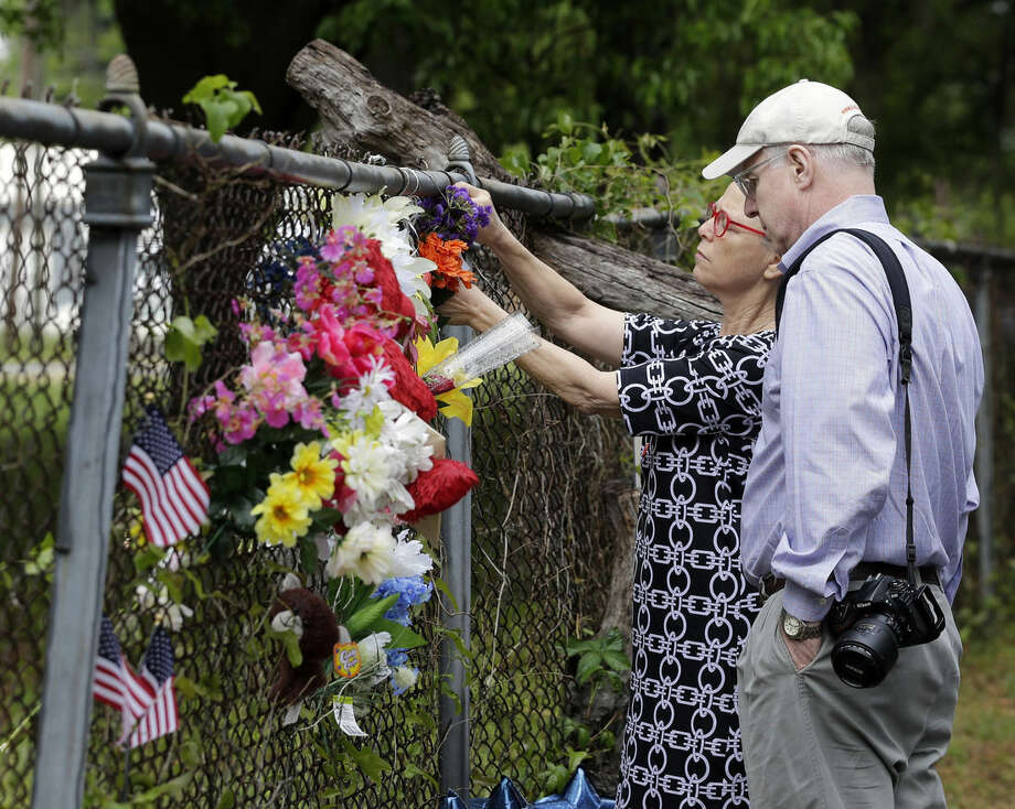 Neda Nussbaum, left, attaches flowers to a fence accompanied by her husband, Alan, in North Charleston, S.C. on Saturday, April 11, 2015 at the scene of Walter Scott's death. Scott was fatally shot a week earlier by a North Charleston police officer after a traffic stop. Officer Michael Slager has been charged with murder. (AP Photo/Chuck Burton)