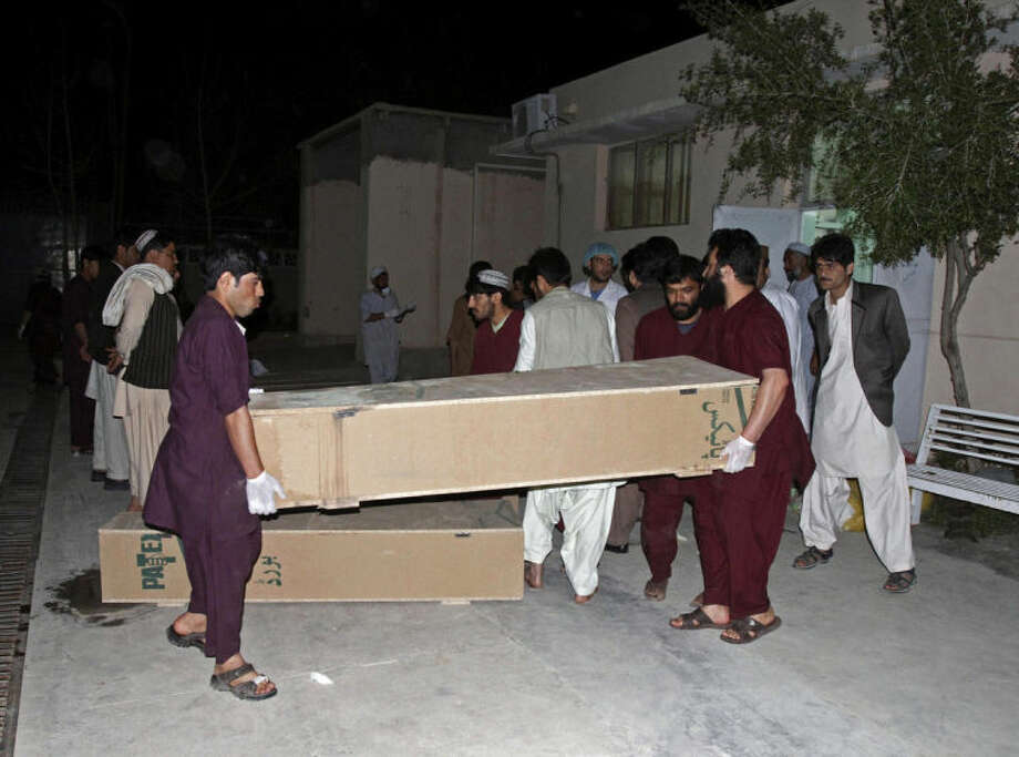 Hospital staff carry the coffin of a person killed from a roadside bomb, at a hospital in Kandahar, south of Kabul, Afghanistan, Monday, April 7, 2014. A roadside bomb killed at least 15 people traveling in vehicles that had been diverted from a main road Monday after an earlier attack in southern Afghanistan, officials said. (AP Photo/Allauddin Khan)