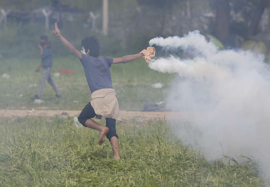 A migrant man throws a can of the tear gas back toward Macedonian police during a protest at the northern Greek border point of Idomeni, Greece, Sunday, April 10, 2016. Thousands of migrants protested at the border and clashed with Macedonian police. (AP Photo/Amel Emric)
