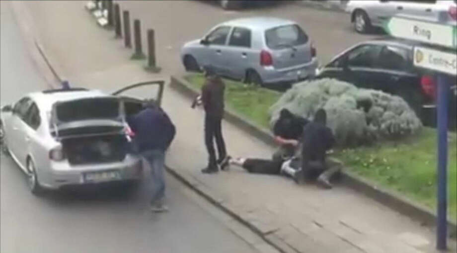 """In this image made from video, police arrest a man in the Anderlecht area of Brussels, Friday, April 8, 2016. A fugitive suspect in the Nov. 13 Paris attacks was arrested in Belgium on Friday, French police officials said, after a raid Belgian authorities said was linked to the deadly March 22 Brussels bombings. The suspect, Mohamed Abrini, is believed to be the mysterious """"man in the hat"""" who escaped the double bombing at the Zaventem airport, according to one of the French officials. (Sebastian Kamran via AP)"""
