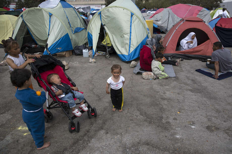 Children play in front of tents at the port of Piraeus, near Athens, on Sunday, April 10, 2016. Migrants clashed with Macedonian police Sunday after trying to scale the fence separating Greece from Macedonia in the border town of Idomeni. (AP Photo/Yorgos Karahalis)